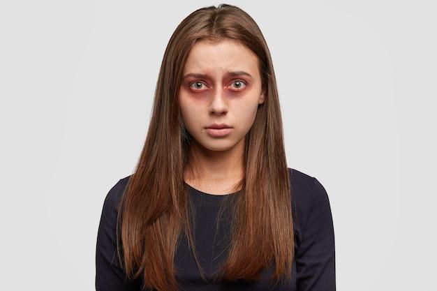 Mujer joven asustada con moretones posando contra la pared blanca