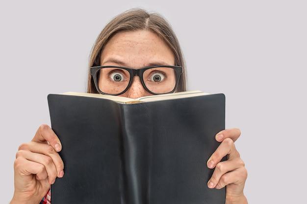 Mujer joven asustada que cubre parte de su rostro con el libro de tapa negro.
