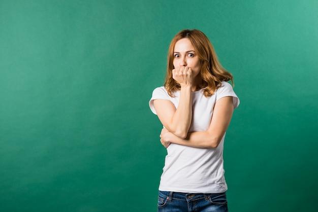 Mujer joven asustada que cubre su boca contra el fondo verde
