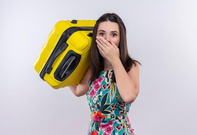 Mujer joven asustada que sostiene la maleta en la pared blanca aislada
