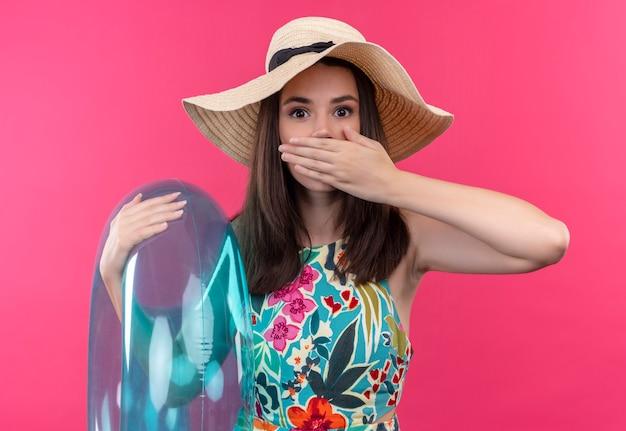 Mujer joven asustada con sombrero sosteniendo el anillo de natación y sosteniendo la mano en la boca en la pared rosa aislada