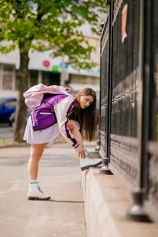 Mujer joven atando los cordones de sus zapatos en sus botas blancas