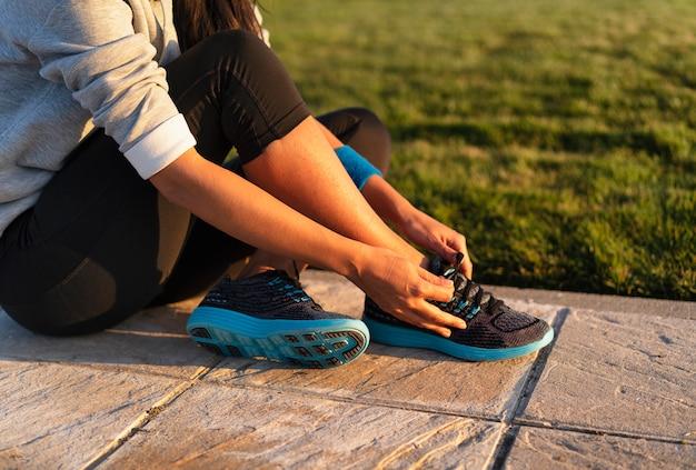 Mujer joven atar los cordones de las zapatillas de deporte para hacer correr el entrenamiento de entrenamiento. fitness y estilo de vida saludable