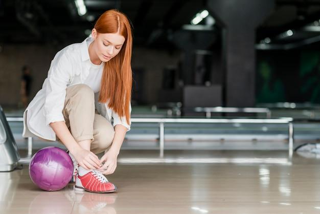 Mujer joven atar cordones de los zapatos en un club de bolos
