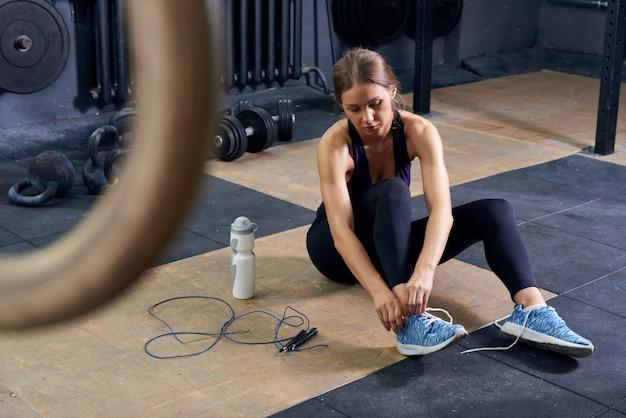 Mujer joven atar zapatos en el gimnasio