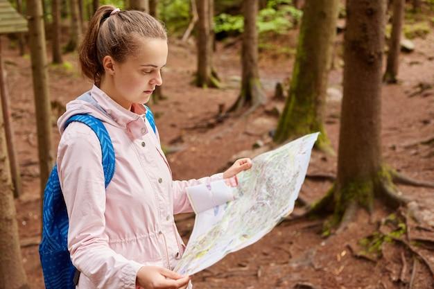 Mujer joven atenta y pensativa con cola de caballo explorando el mapa de viaje, eligiendo la forma de movimiento, comenzando una nueva aventura durante las vacaciones