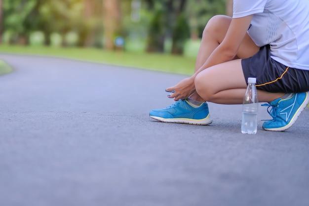Mujer joven atleta atar zapatillas en el parque al aire libre