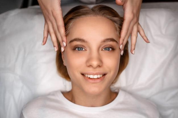 Mujer joven atractiva alegre que miente en el sofá blanco. esteticista toca su rostro con las manos desnudas. modelo sonríe y mira directamente.