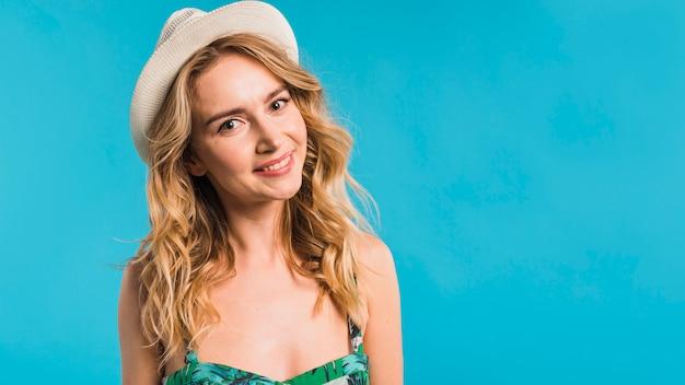 Mujer joven atractiva alegre en vestido y sombrero florecidos
