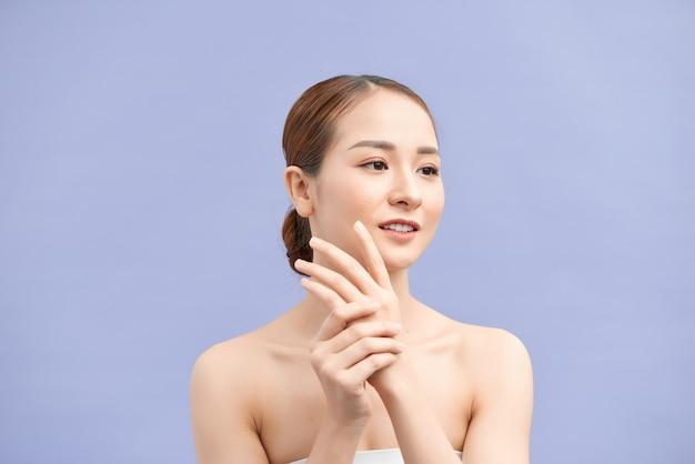 Mujer joven atractiva aplicar crema de manos en violeta