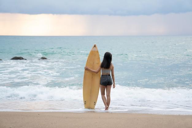 Una mujer joven atractiva asiática que camina en la playa con la tabla hawaiana en phuket tailandia