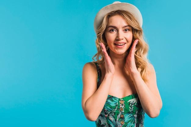 Mujer joven atractiva asombrada en vestido y sombrero florecidos