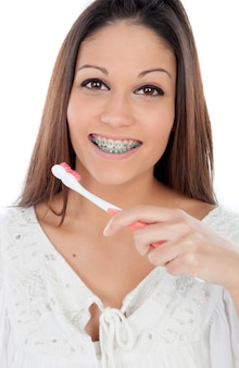 Mujer joven atractiva con brackets limpiar sus dientes