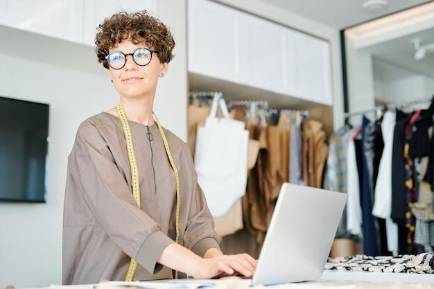 Mujer joven atractiva con cabello rizado oscuro escribiendo en el teclado de la computadora portátil mientras piensa en nuevas ideas creativas