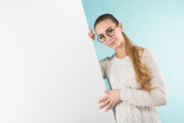 Mujer joven atractiva con cartel en blanco