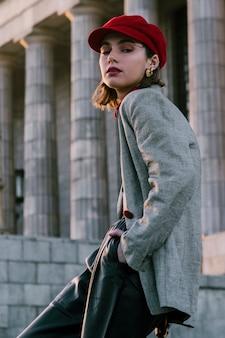 Una mujer joven atractiva en casquillo rojo con sus manos en el bolsillo que mira la cámara