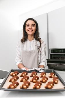 Mujer joven atractiva cocinar sabrosas galletas en una bandeja mientras está de pie en la cocina