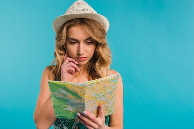 Mujer joven atractiva concentrada en el sombrero que mira el mapa
