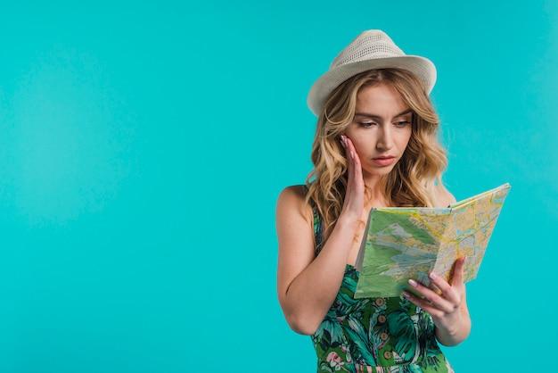 Mujer joven atractiva concentrada en el sombrero y el vestido que miran el mapa