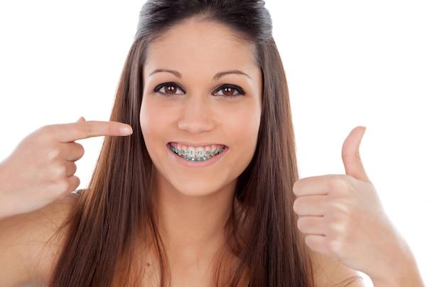 Mujer joven atractiva con corchetes diciendo ok