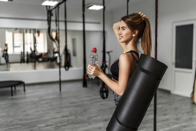 Mujer joven atractiva con una estera de yoga y una botella de agua en un moderno gimnasio ligero