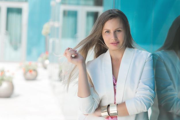 Mujer joven atractiva con estilo de negocios al aire libre. empresaria al aire libre. todavía de señora con chaqueta blanca con espacio de copia.