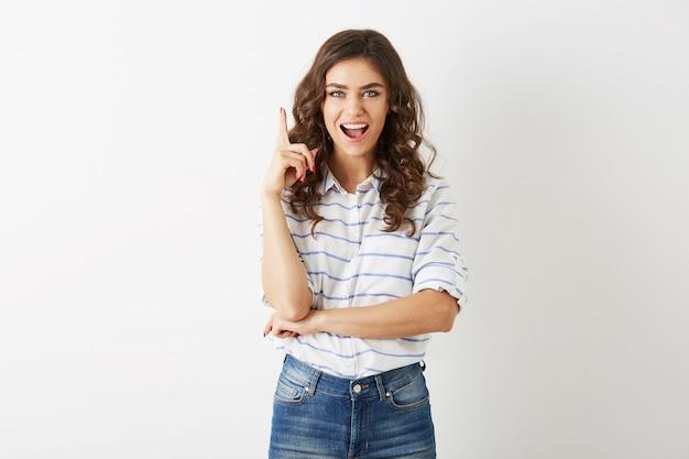 Mujer joven atractiva con expresión de la cara emocionada que tiene la idea de levantar el dedo, estilo casual adolescente, cabello rizado, emoción positiva, mirada sorprendida, aislado