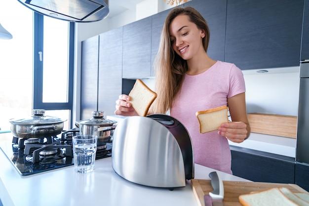 Mujer joven atractiva feliz que usa la tostadora para hacer tostadas del desayuno en la cocina en casa temprano en la mañana. aparato electrodoméstico y de cocina para cocinar