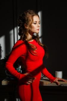 Mujer joven atractiva hermosa en un vestido rojo en un fondo gris