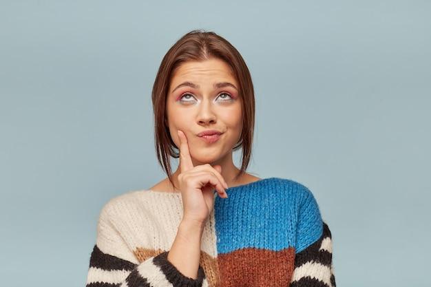 Una mujer joven y atractiva con un hermoso maquillaje vestida con un suéter multicolor está pensativa sosteniendo un dedo cerca de su mejilla.