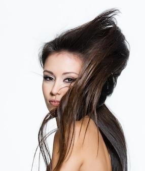 Mujer joven atractiva con hermoso peinado largo creativo, posando aislado en blanco