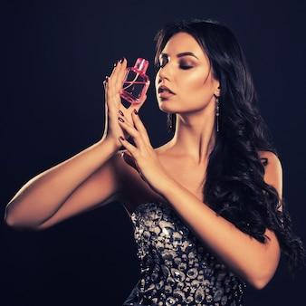 Mujer joven atractiva con un hermoso vestido con perfume en el espacio oscuro.