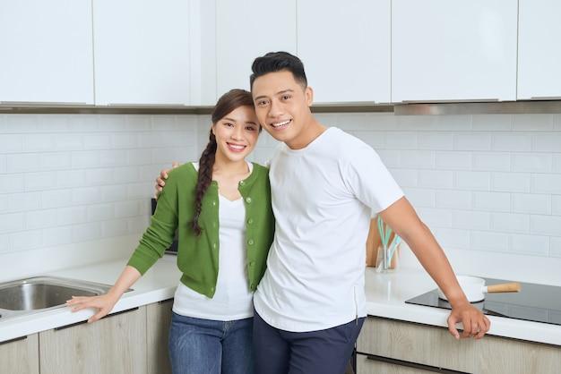 Mujer joven atractiva y hombre guapo disfrutan de pasar tiempo juntos mientras están parados en la cocina moderna y ligera.