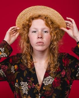 Mujer joven atractiva del jengibre que pone en el sombrero de paja