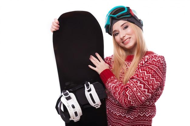 Mujer joven atractiva en jersey rojo y gafas de esquí azules sostienen snowboard
