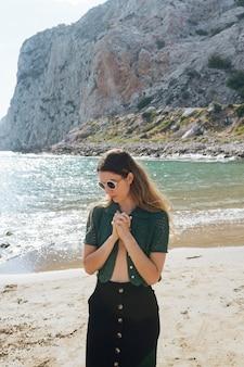 Mujer joven atractiva con la mano abrochada de pie en la playa
