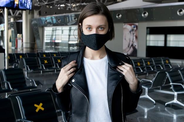 Mujer joven atractiva con una máscara protectora negra con una mochila en la terminal del aeropuerto internacional. viajar durante la pandemia de coronavirus.