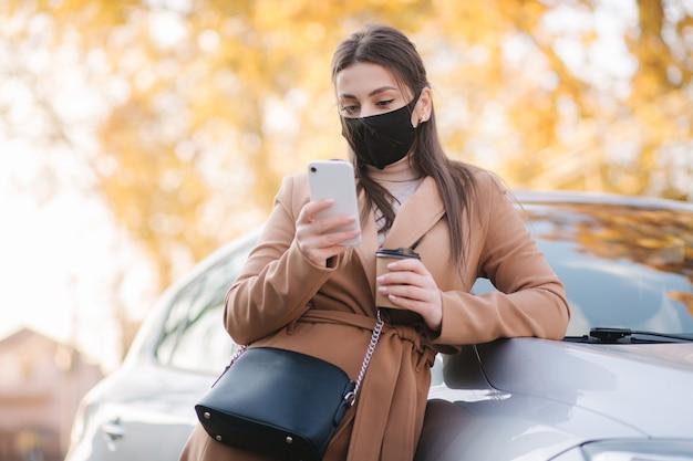 Mujer joven atractiva en máscara protectora con taza de café junto al coche y teléfono de uso.