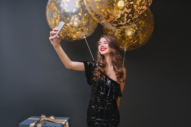 Mujer joven atractiva con peinado rizado haciendo selfie en habitación con interior negro durante la fiesta. chica caucásica rubia refinada celebrando cumpleaños y riendo.