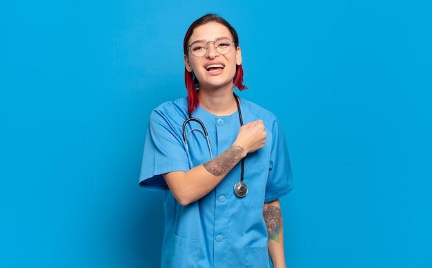 Mujer joven atractiva pelirroja que se siente feliz, positiva y exitosa, motivada al enfrentar un desafío o celebrar buenos resultados. concepto de enfermera del hospital