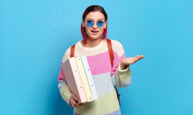 Mujer joven atractiva pelirroja que se siente feliz, sorprendida y alegre, sonriendo con actitud positiva, dándose cuenta de una solución o idea. concepto de estudiante universitario