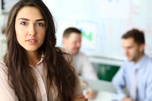 Mujer joven atractiva con el pelo largo de pie en la oficina