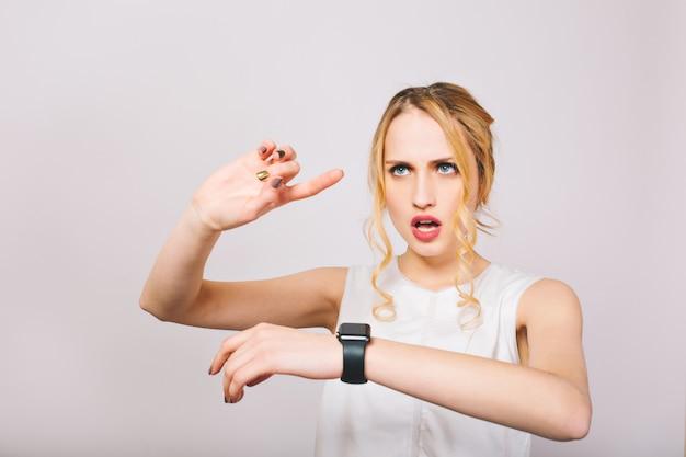 Mujer joven atractiva con el pelo rizado con blusa elegante mira reloj de pulsera negro y planes de día. encantadora dama rubia en camiseta blanca recuerda la lista de casos para hoy y calcula el tiempo.