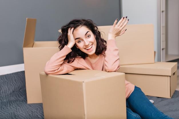 Mujer joven atractiva con el pelo rizado moreno corto que expresa el cartón circundante en apartamento moderno. disfrutando de la reubicación, mudarse a un nuevo hogar, verdaderas emociones felices