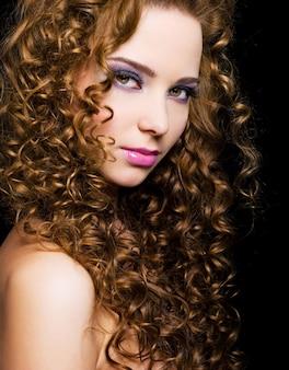 Mujer joven atractiva con pelos largos rizos - aislado en negro