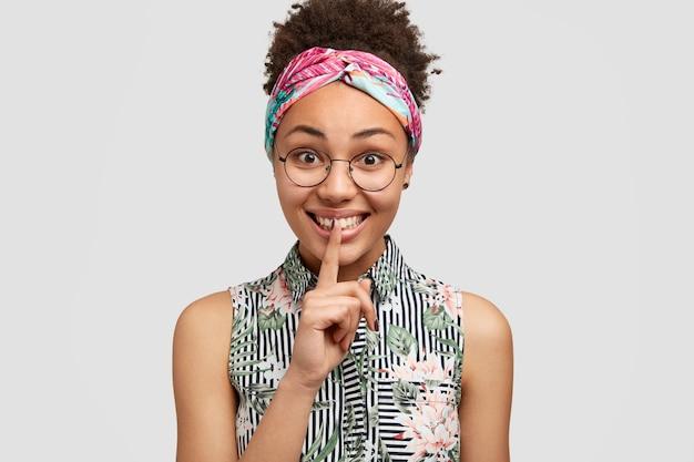 Mujer joven atractiva con piel oscura pura, expresión positiva, hace gesto de silencio y dice shh