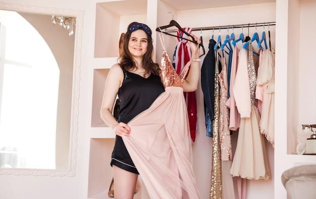 Mujer joven atractiva en pijama negro está eligiendo ropa en la sala de luz y mira a cámara. chica en armario.