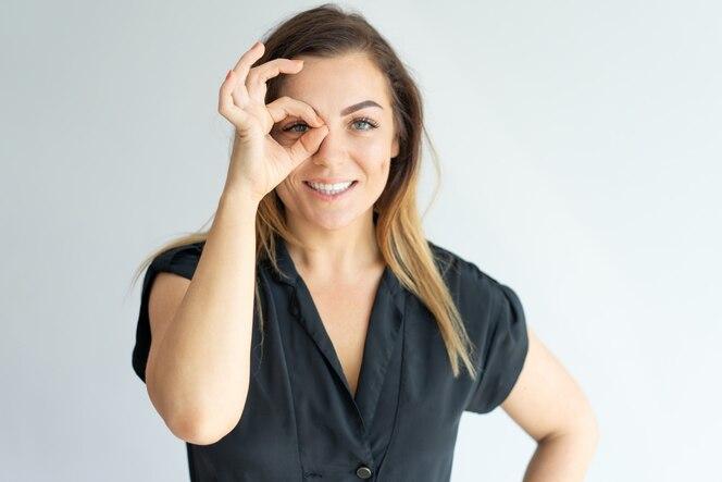 Mujer joven atractiva positiva que hace la muestra aceptable y que mira a través de los dedos en la cámara.