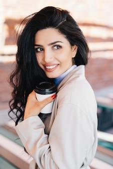 Mujer joven atractiva que bebe la bebida caliente de la taza de papel disponible que tiene el pelo oscuro perfecto