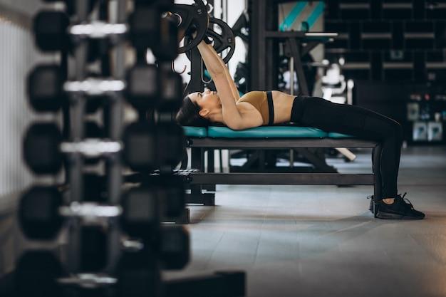 Mujer joven atractiva que ejercita en el gimnasio